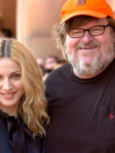 "Madonna poses with Michael Moore at the screening of her documentary, ""I Am Because We Are"""