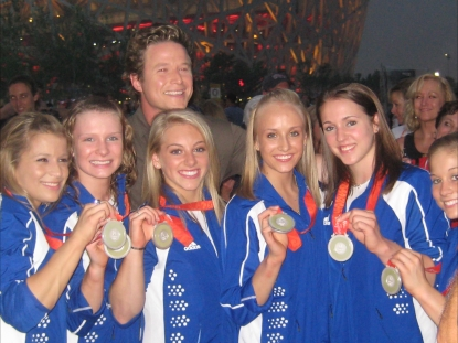The women's gymnasts show off their silver to Billy