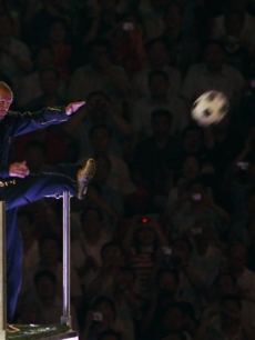 David Beckham kicks a ball during the closing ceremony for the 2008 Beijing Olympics