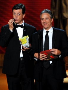 Stephen Colbert enjoys a snack while presenting with Jon Stewart