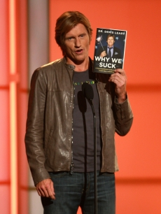 Denis Leary holds his 2008 book, 'Why We Suck' on stage in NYC, Sept. 5