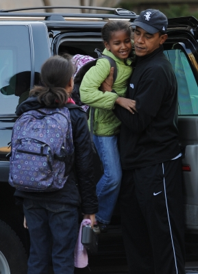 Barack hold Sasha as he drops the girls off at school