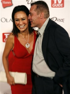 What is Tom Sizemore whispering in Tia Carrere's ear?