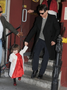 Suri leads her dad, Tom Cruise, out of a restaurant in NYC, Nov. 28, 2008