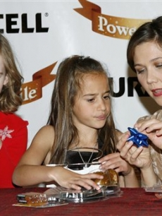 Maggie Gyllenhaal with young Duracell Holiday Ambassadors, Grace N., left, of Rogers, Ark., and Nikay W., center, of Albuquerque, N.M., gift wrapping toys in New York