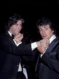 John Travolta and Sylvester Stallone exchange mock punches at the Dorothy Chandler Pavillion in Los Angeles, California, April 1978