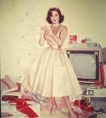 Elizabeth Taylor poses in front of an artificial tree, 1950s