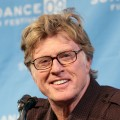 Robert Redford smiles for the press during Sundance's opening day