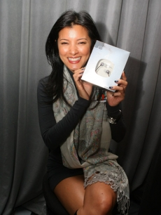 Kelly Hu holds up her Ultimate Ears by Logitech earphones