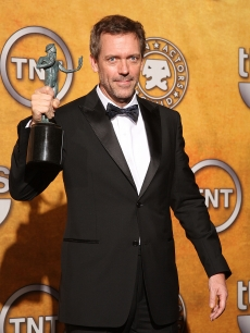 Hugh Laurie poses with his award for Outstanding Performance by a Male Actor backstage