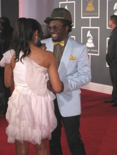will.i.am shares a smile with a reporter on the red carpet at the Grammys
