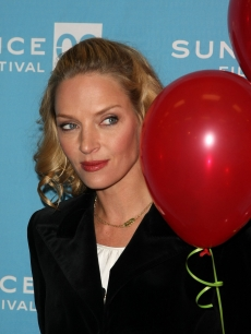 Uma Thurman hides behind some red balloons