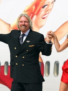 Richard Branson poses with Kate Moss on a wing of a jumbo jet in celebration of Virgin Atlantic's 25th birthday on June 22, 2009 in London