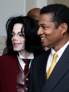 Michael Jackson and his brother Jackie Jackson smile as they re-enter the courtroom after a break for Michael Jackson&#8217;s child molestation trial at the Santa Barbara County Courthouse in Santa Maria, California on April 27, 2005 