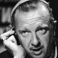 Closeup of Walter Cronkite speaking while listening to a headset circa 1968